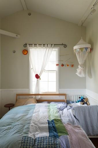 親子三人の寝室。屋根の勾配がわかる三角の天井が空間のアクセントに。