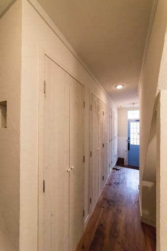 玄関から続く廊下の脇にたっぷりとした収納スペース。廊下の壁も扉も、自分たちでペンキを塗っているのだそう。