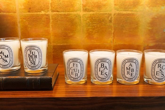 """フレグランスキャンドル 左からMIMOSA(ミモザ) TUBEREUSE(テュベルーズ) FIGUIER(フィギエ) BAIES(ベ)AMBRE(アンブル)  ROSES(ローズ) 以上190g 各¥6,825 人気の6モデル。フローラルの香りのミモザ、 テュベルーズ、ローズ、フルーティな香りのべ、フィギエ、ウッディな香りのアンブル。一番人気は""""ベ""""。"""