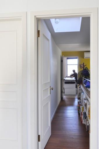 奥のリビングから表側のリビングを見る。途中の子ども部屋にはアクセントとして黄色が塗られている。