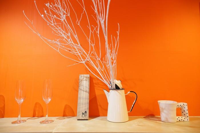 オレンジの壁に造り付けられた棚には、食器などが並ぶ。「オレンジ色に塗ったのは、もともとの石膏ボードが黄色で、水まわりはあたたかな色がいいなと思ったから」。