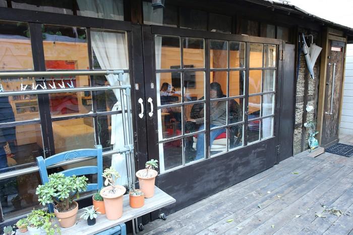 ウッドデッキからの外観。ドアの外側は焦げ茶色にペイントした。写真の奥の扉が玄関。玄関扉の手前の竹小舞土壁が、建設当時を物語る。