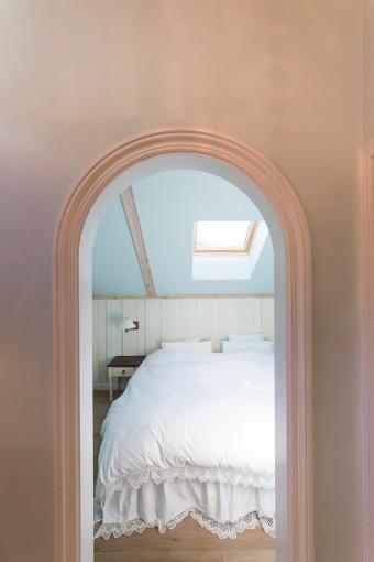 ベッドルームはブルーで塗装し、シンプルに。天窓から星空が眺められる。入口はアーチ型にこだわった。