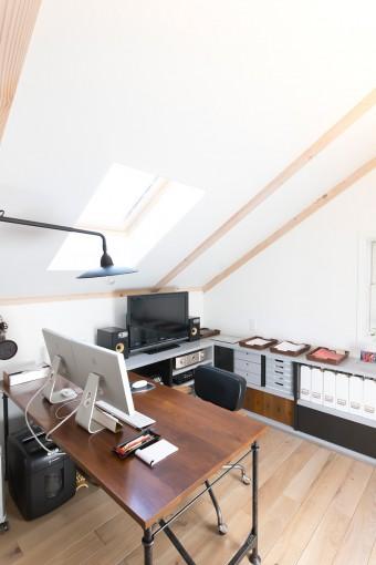 真也さんのワークスペース。天窓から光が差し込んで明るい。デスクや収納棚を造作し、仕事のはかどる機能的なスペースに。