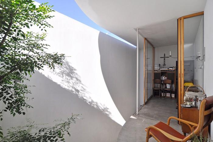 2階リビング。その奥にキッチン。壁に落ちる影が1日の中で様々に変化しその多彩な表情で楽しませてくれる。
