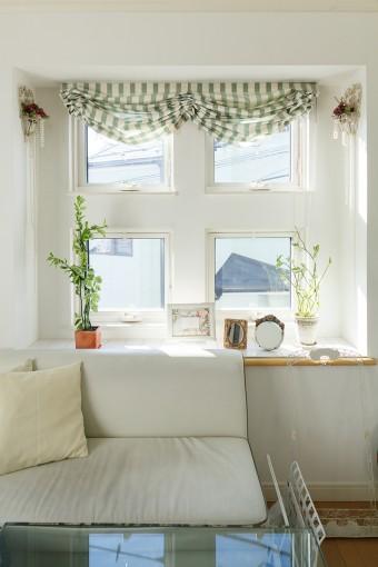 四つ並んだ窓がかわいらしい出窓が主役のリビングは、白を基調にグリーン系でコーディネート。の天井が窓から午後の光がたっぷりと降り注ぐ。