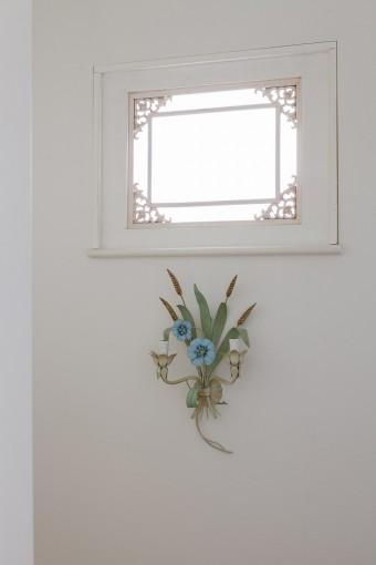 お気に入りの木彫りのフレームをいかすために、窓のサイズにピッタリの木枠をオーダーで作ってもらった。下のブルーの花のランプはヨーロッパのアンティーク。