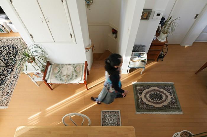 リビングからキッチンへ向う博子さんを、アトリエから見る。クム産のペルシャ絨毯をリビングダイニングのあちこちに敷いている。