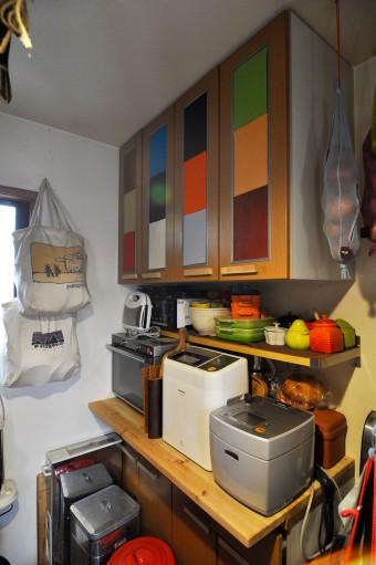 キッチンの棚もいろんな色の布を使ってチェンジ。シルバーの取っ手も気になって、木に付け替えた。