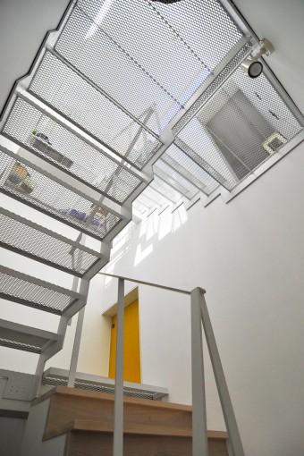 階段の踏み面はより多くの光を1階まで落とすためにエキスパンドメタルを採用。