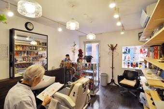 照明をはじめ、昭和レトロな雰囲気にこだわった店舗部分。手前は公世さんのお母様。昭和32年から床屋を続けられている。