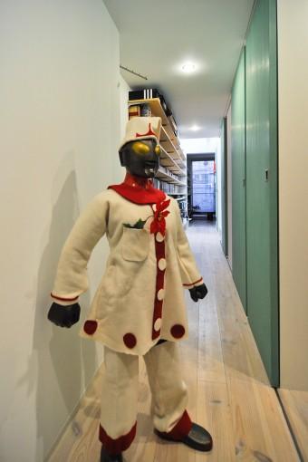 1階の店舗側から奥を見る。クリスマスヴァージョンの服を着たウルトラマンの後ろにはマンガなどを収めた棚が長く続く。