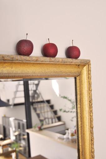 友人からの贈り物という大きな鏡のフレームの上に、小さな赤いリンゴが3つ。