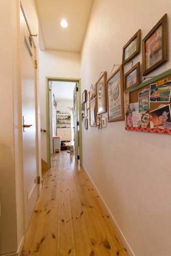 廊下の壁面を家族のフォトフレームで飾る。床は無垢のパイン材を選択。