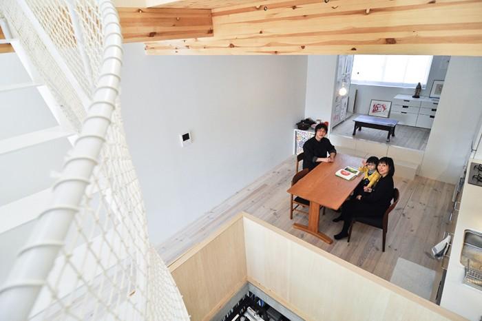 螺旋階段の途中からダイニングの一家を見る。奥のスペースはいずれ、子ども部屋か夫妻の寝室になるという。その床下は収納スペースになっている。