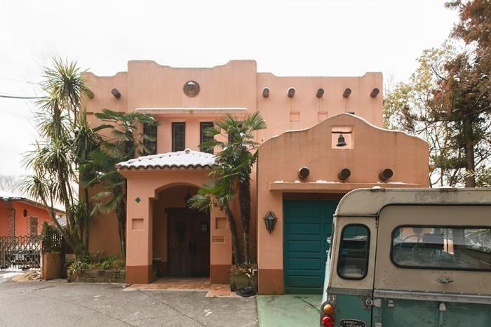 外観。右手前のブルーの扉の先がガレージで、その奥がキッチンにつながっている。左手の玄関ドアは、サンタフェで入手したもの。