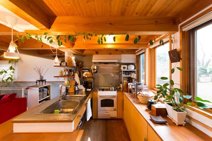 窓から庭が見渡せるキッチン。天井をマダガスカルジャスミンが這う。コンロは4つ口にこだわり、フランスのロジェールを採用。
