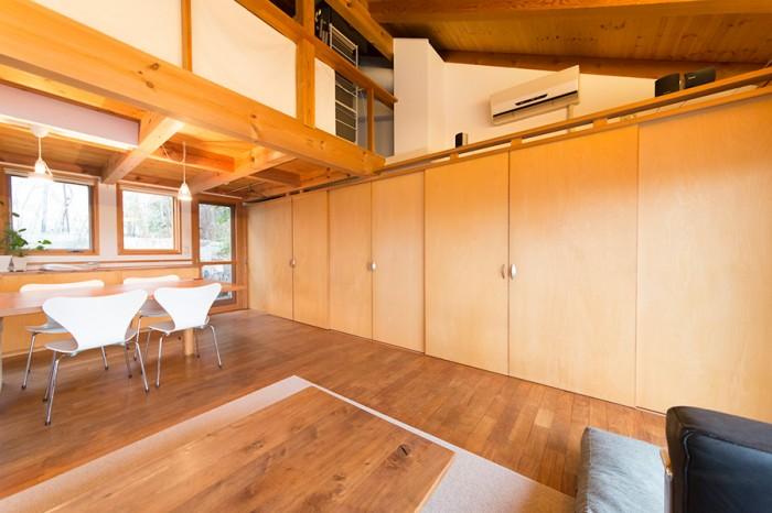 一面に取り付けた収納庫。開けるとテレビ、洗濯機、冷蔵庫が。上のロフトにつながる階段もある。