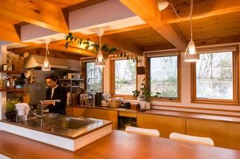 天井の梁がナチュラル感を出す。ダイニングテーブルは無垢の厚手の板で造り付けにした。