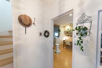 玄関からリビング、2階にあがる階段をのぞむ。白い壁面に、照明の陰影が映し出される。
