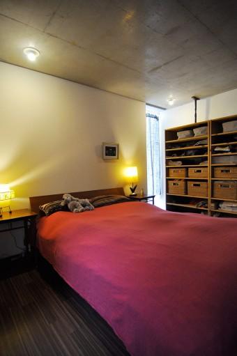 ベッドルームはファブリックで色を添えて。収納はあえてオープンにして、無駄なものを溜め込まないようにしている。