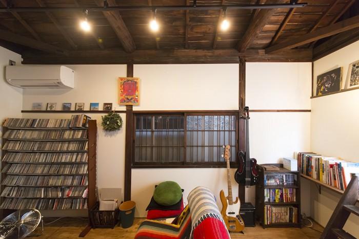 2階リビングには、バンド活動を続けるサノさんの楽器やCDがずらりと並ぶ。正面の建具が、この家でずっと使われてきたもの。
