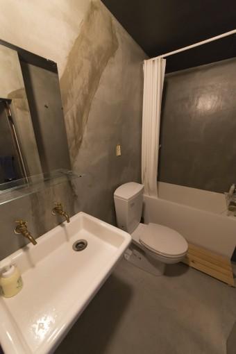 水回りはモルタル仕上げのモダンなデザイン。壁の補修も味として見せている。