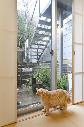 """1階の和室で雨が降る外を見るジャン。一家の""""精神的支柱""""というジャンの名前は、ジャン=ポール・サルトルから取られた。"""