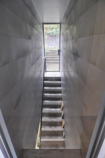 地下(道路のレベル)から1階へと上がる階段。1回外に出てから家に入る。