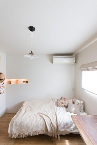 ベッドルームはシンプルに。夜はアンティークのランプとニッチの灯りがやさしく灯る。