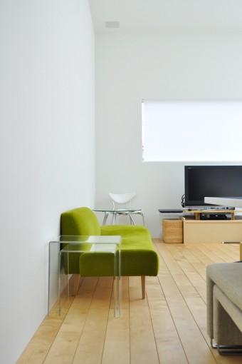 竣工後、熟考を重ねて購入されたというソファ。品のいい緑の色合いが白基調の室内に美しく映える。