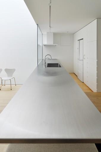 キッチンから連続したダイニングテーブル。食事などの際にはこの下に納められた木の椅子を引き出して座る。