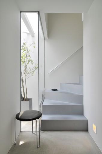 玄関を上って1階の床は左の外部空間と同じコンクリート仕上げ。近い色合いの階段とのつながりも自然だ。