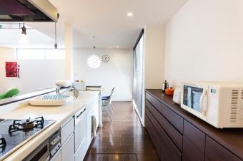 整然と片付けられたキッチン。収納は床の茶色に揃え、家電は白で統一。