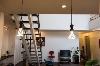 キッチンから眺めるリビング。プルーメンの電球は、カフェなどでも使われている。