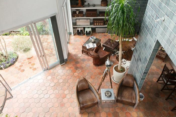 2階からリビングを見下ろす。リビングにも庭にも同じテラコッタタイルを敷いているため、内と外に連続性が生まれている。