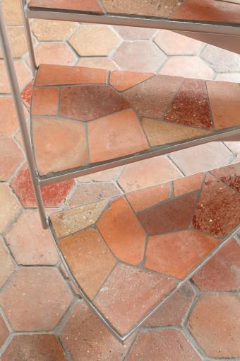 特注のらせん階段。踏み板には床材と同じてラッコタイルを砕いて使った。「砕いたタイルの色や形のバランスをとるのに、左官の職人さんがとても苦労していました」(Tさん)。