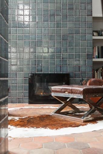 南側の壁に設えた暖炉。煙路は天井までフランス製のブルーのタイルで覆われている。