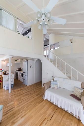 天井高のある開放的なリビング。白い空間にシーリングファンが、どこかコロニアルの雰囲気。