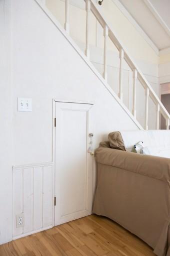 階段の手すりは抜け感のあるものに付け替え、新しく収納スペースも確保した。ドアも壁と同じく白く塗装。