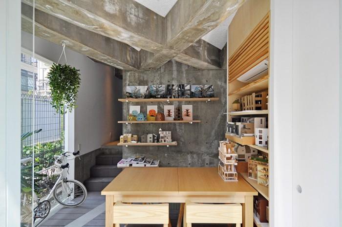 オープンな佇まいの1階の打ち合わせスペースの正面の棚には、道行く人の目を引き付けるポップな色合いの建築模型と写真が飾られている。