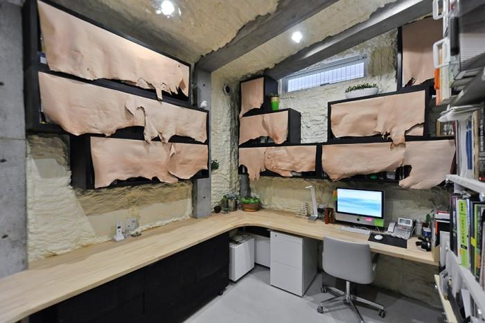 地下の事務所スペースは、地中に根を張っている中で仕事をしているようなイメージでつくられた。壁は土をイメージした発泡ウレタン。棚に付けられたカバーは暖色の豚皮。「地下に住むナントカ民族みたいな感じを出したかった」という。