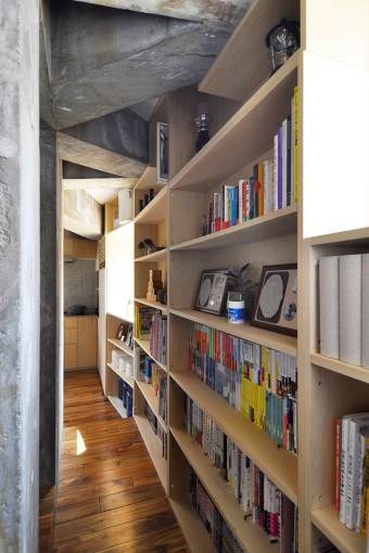 2階のキッチンへと至る廊下には本棚を配し、スペースを効率的に使用。