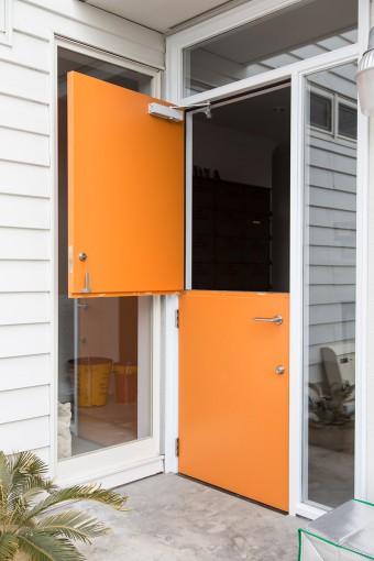 オレンジ色がキュートな玄関ドアは、上半分だけ開けることができる。「機能というより、遊び心重視のデザインです」