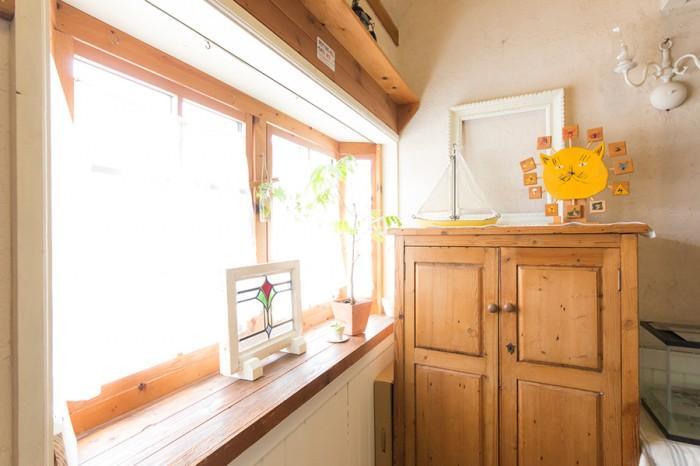 玄関ホールの戸棚も、美紀さんの作。棚の上のネコの時計は、息子さんが幼いときにつくったもの。