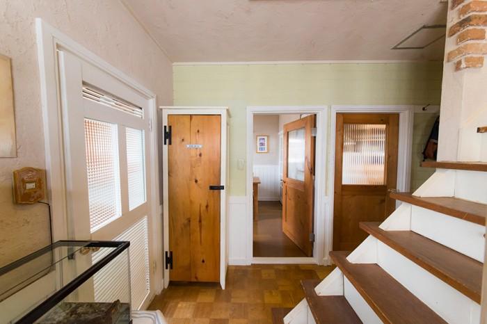 手前の白い扉は洗面所へ、奥の2枚の扉はダイニングとリビングへ続く。ドアにはデッドストックのガラスをはめこんでいる。