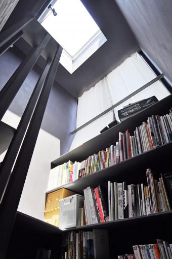 階段と一体にしてつくられたスチール製の本棚。トップライトから光が落ちる。