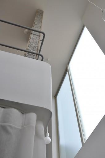 スチールの手すりのカーブと、白い床面を覆う素材のカーブの角度が揃っているのが美しい。窓は光が拡散するスリガラスを採用。