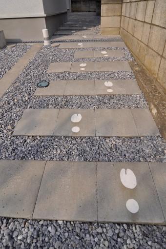 敷石の上に転々と続く足跡。マルジェラのデザインしている二股の靴の跡になっている。
