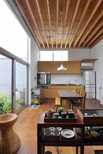 3.8mと高めの天井が気持ちの良い姉夫婦のキッチンとダイニング。左に中庭。